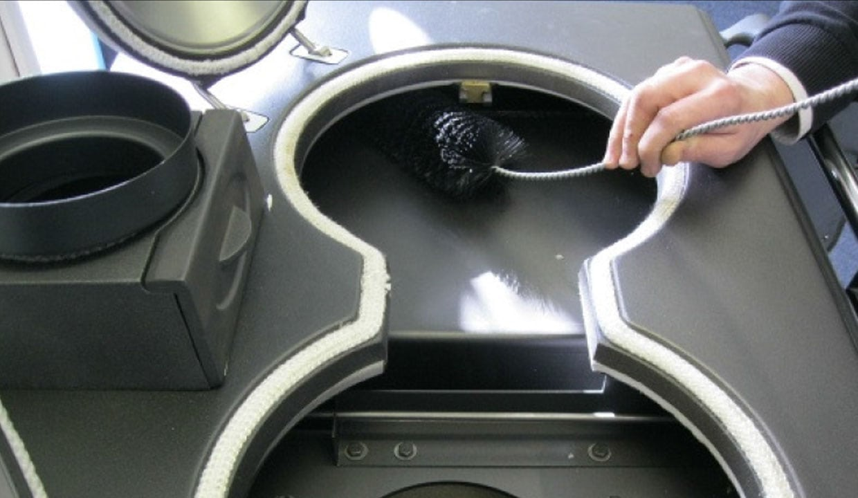 cleaning your cooker with flue brush