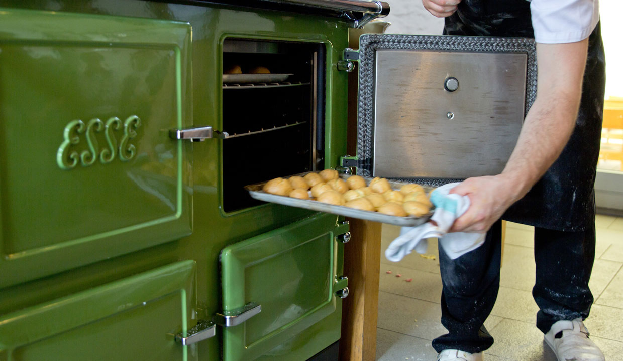Tray of food being placed into the oven of a green esse range cooker