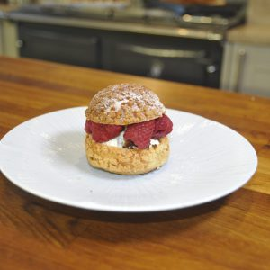 Choux buns with white chocolate ganache, raspberry and salted pistachio